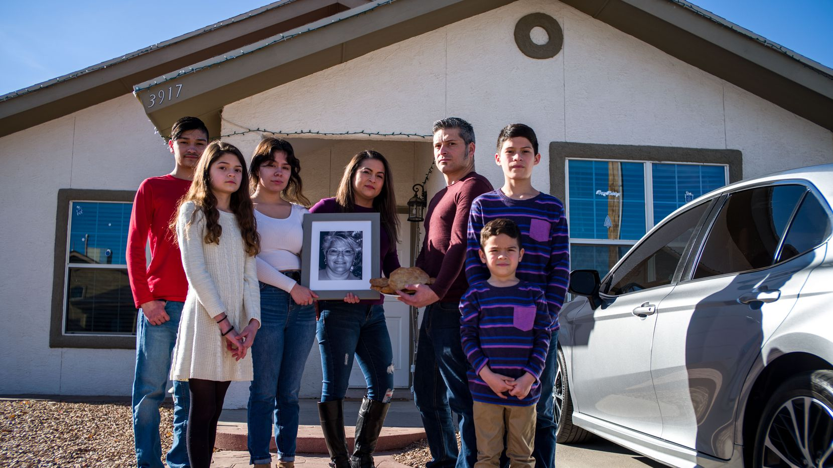 Christopher Martínez, 13, his sister Maya Martínez, 12, cousin Jasmine Martínez, 19, mother Muriel Martínez, 33, father Armando Martínez, 35, brother Sebastian Martínez, 5, and cousin Diego Martínez, 13, pose for a portrait outside their home as they gather around a photograph of Christopher's grandmother Maria Oralia Lugo, 56, in El Paso on Dec., 17, 2020. Maria Oralia Lugo and two other relatives died of COVID-19 in November.