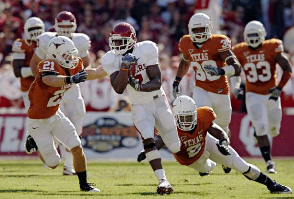 Oklahoma running back DeMarco Murray (center) finds a pocket between Texas safety Blake Gideon (21) and linebacker Sergio Kindle during the first half of Texas' 16-13 win Saturday, October 17, 2009 at the Cotton Bowl in Dallas.