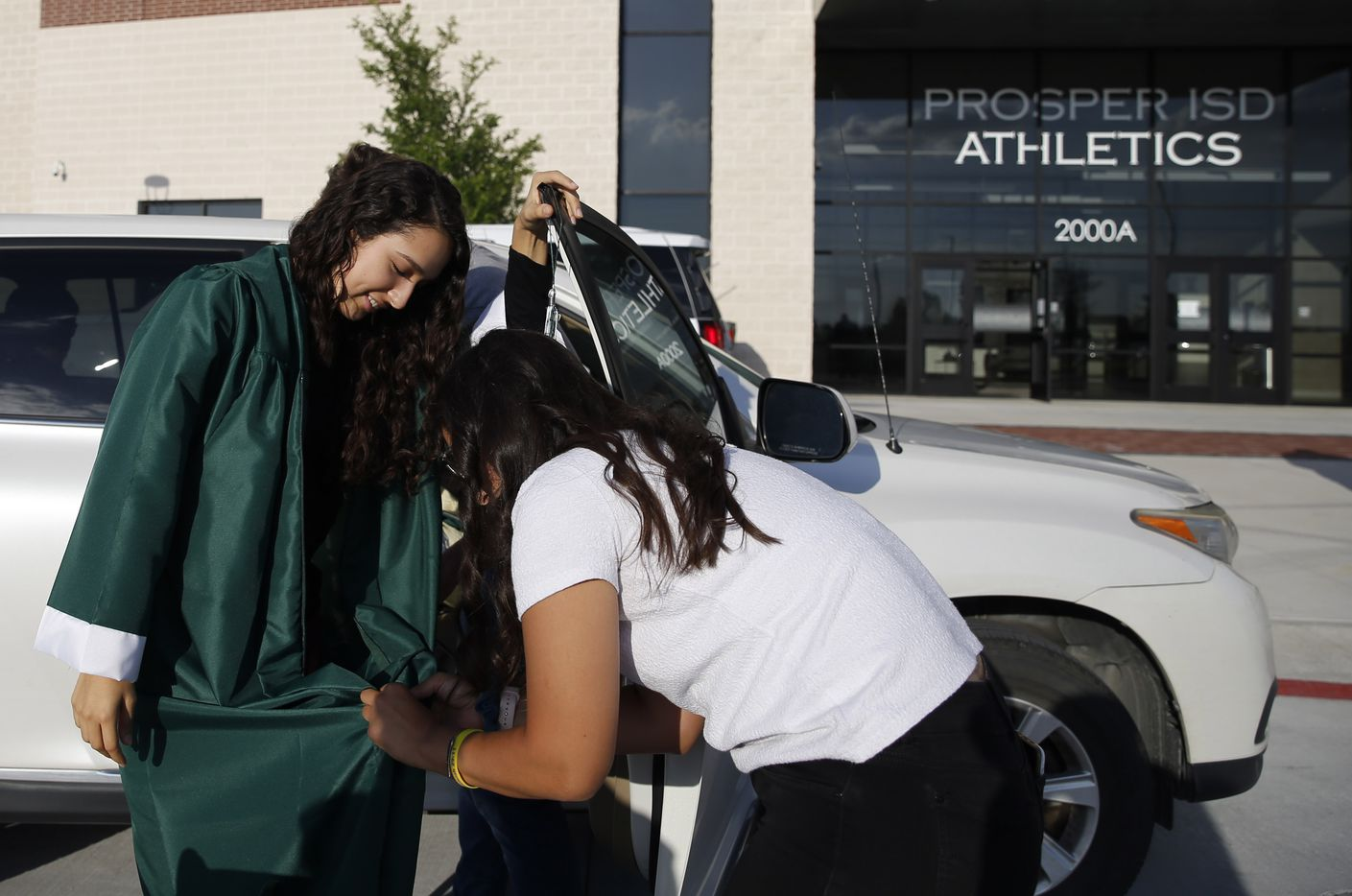 Prosper High School softball player Lexie Bell gets help from her sister Tori Bell with her gown prior to Prosper High School's graduation ceremony at Children's Health Stadium in Prosper, Texas on Friday, June 5, 2020. Bell signed to play softball at St. Edward's University. But she was recently diagnosed with Ewing Sarcoma, a rare form of cancer.