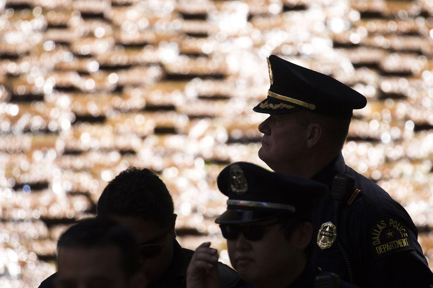 Members of the Dallas police department are silhouetted against the water cascading down the Great Fountain during a day of remembrance for last year's police ambush organized by Faith Forward Dallas at Thanks-Giving Square on Friday, July 7, 2017, in Dallas. Friday marked the one-year anniversary of the attack which killed five police officers.