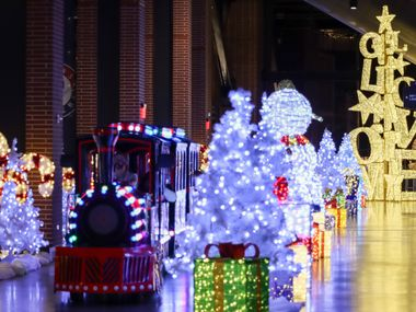 A train carries guests around Christmas decorations and sculptures at Luminova Holidays at Globe Life Field in Arlington. A Christmas decor store in the city is seeing steady traffic as people adapt to celebrating the holidays during the COVID-19 pandemic.