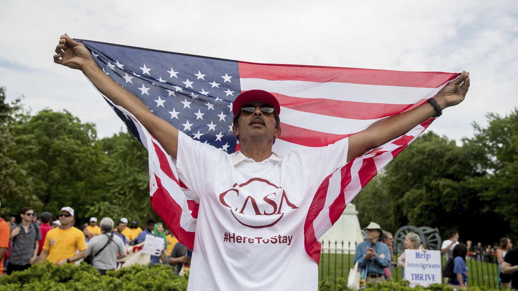 Alejandro Ángeles, de Greenbelt, Maryland, levanta una bandera norteamericana mientras que se une a un grupo de manifestantes afuera de la Casa Blanca en contra del presidente Donald Trump. (AP/ANDREW HARNIK)