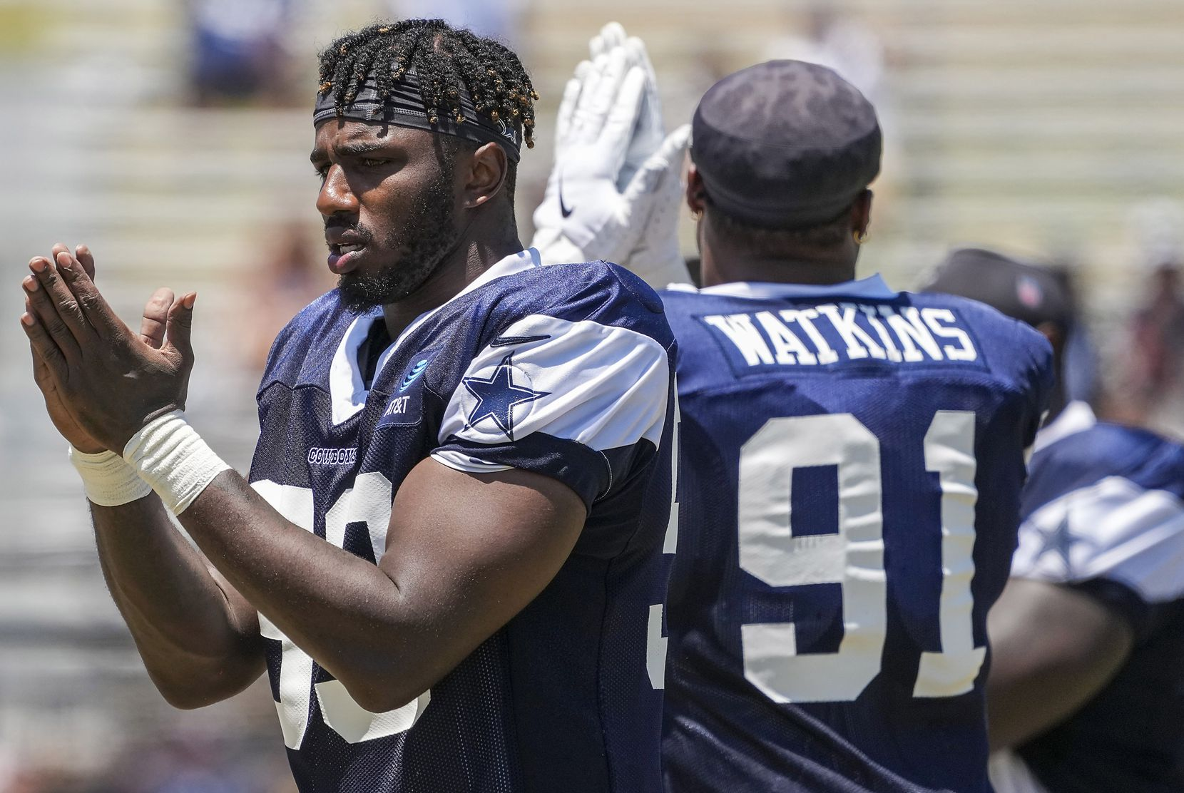 Dallas Cowboys defensive end Tarell Basham (93) and defensive end Carlos Watkins (91) signal a play during a practice at training camp on Wednesday, July 28, 2021, in Oxnard, Calif.
