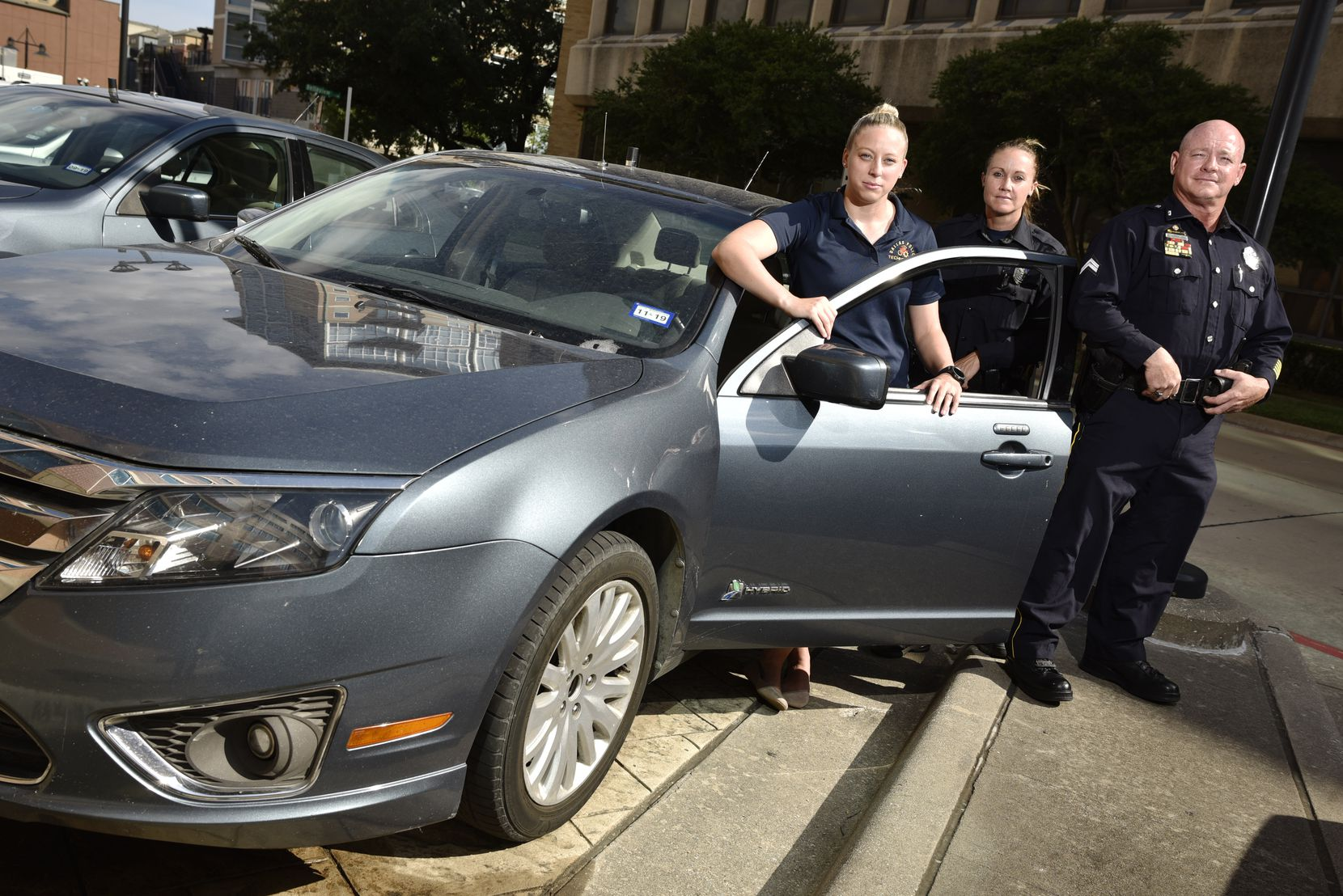 L-R: Dallas Police Officers with the Mobile Surveillance Unit, Manager Emily Davis, left, Tara Smith, and Kenneth Strauss, pose with a DPD unmarked vehicle (not a bait car) outside of DPD headquarters in Dallas.