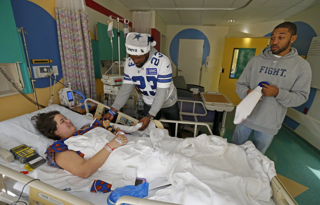 Cowboys players Robert Turbin, left, and Orlando Scandrick, right, visit Rebecca Babler while the Cowboys players and cheerleaders deliver holiday gifts to patients at Texas Scottish Rite Hospital for Children on Wednesday, Dec. 2, 2015, in Dallas. (Jae S. Lee/The Dallas Morning News)