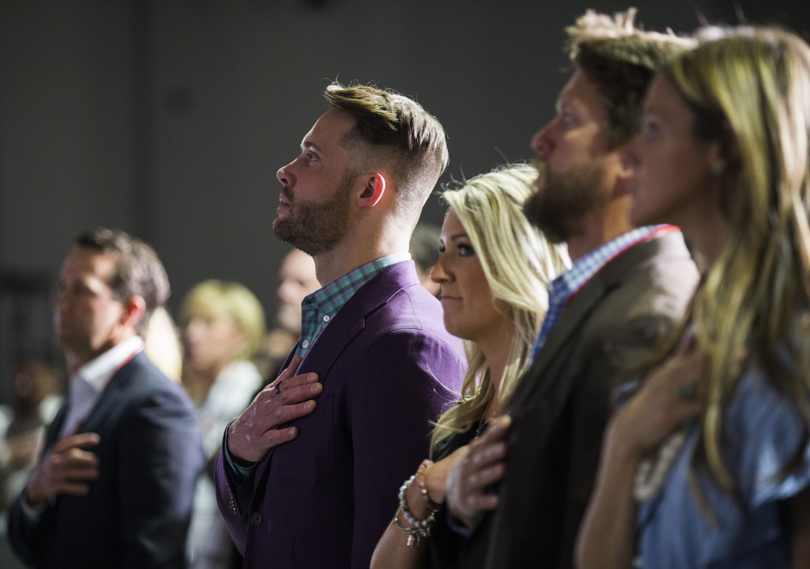 Founder and owner David Vobora places his hand over his heart as the national anthem plays during the opening of the Adaptive Training Foundation nonprofit gym and rehabilitation facility.