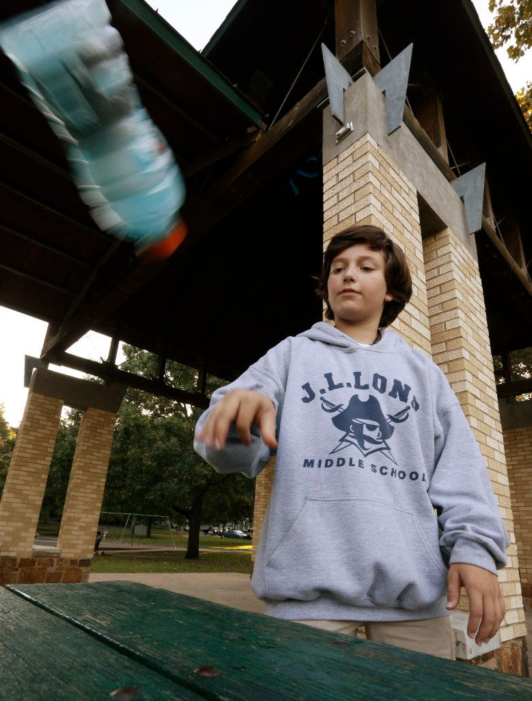 Ian Interrante, 12, demonstrates the flipping bottles game at Lindsley Park in Dallas.