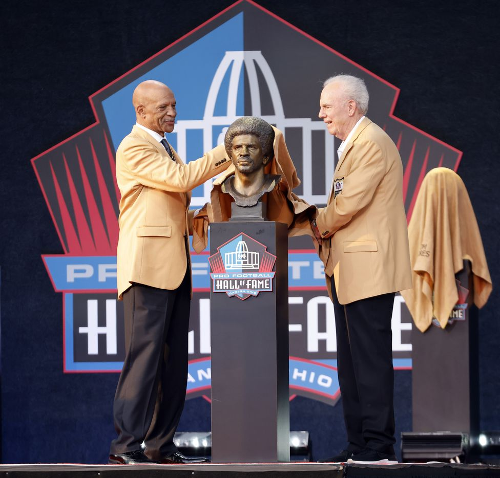 Pro Football Hall of Fame inductee Drew Pearson of the Dallas Cowboys (left) unveils his bronze bust with presenter and former Cowboy Roger Staubach during the Class of 2021 enshrinement ceremony at Tom Benson Hall of Fame Stadium in Canton, Ohio, Sunday, August 8, 2021. (Tom Fox/The Dallas Morning News)