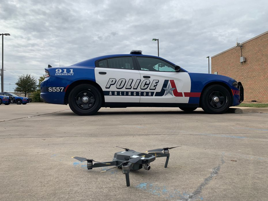 An unmanned aircraft used by Arlington Police in front of an Arlington squad car. The Arlington Police Department began operating drones in 2013.