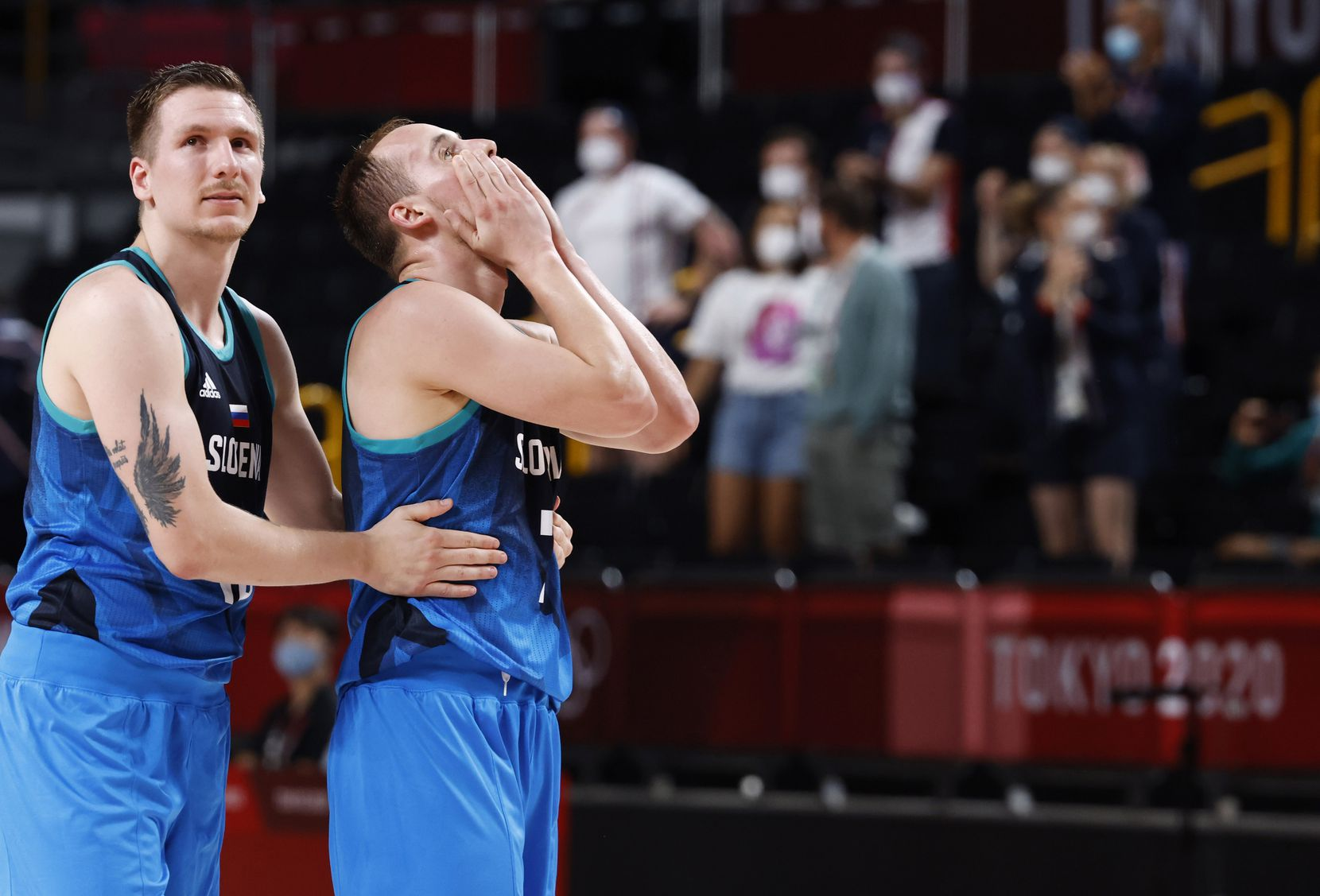 Slovenia's Gregor Hrovat (15) consoles Slovenia's Klemen Prepelic (7) after they lost to France in the final seconds of the second half of a men's basketball semifinal at the postponed 2020 Tokyo Olympics at Saitama Super Arena, on Thursday, August 5, 2021, in Saitama, Japan. France defeated Slovenia 90-89. Slovenia will play in the bronze medal game. (Vernon Bryant/The Dallas Morning News)