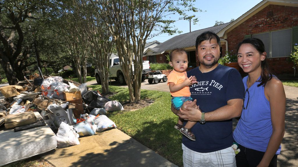 Troy and Catherine Pham and 13-month-old Aidan outside their flood-damaged home in the Meyerland section of Houston after Hurricane Harvey, on Sept. 9, 2017.