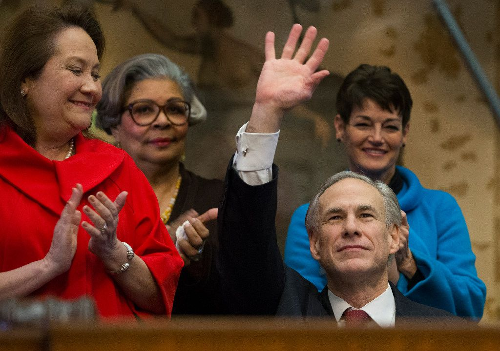 Gov. Greg Abbott, with wife Cecilia at left, waved to lawmakers before giving his state of the state speech and unveiling his proposed budget Tuesday. (Stephen Spillman/The Associated Press)