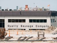 The Quality Sausage Company's location at 1925 Lone Street Drive in Dallas, Texas, partially obstructed by an ongoing construction project.