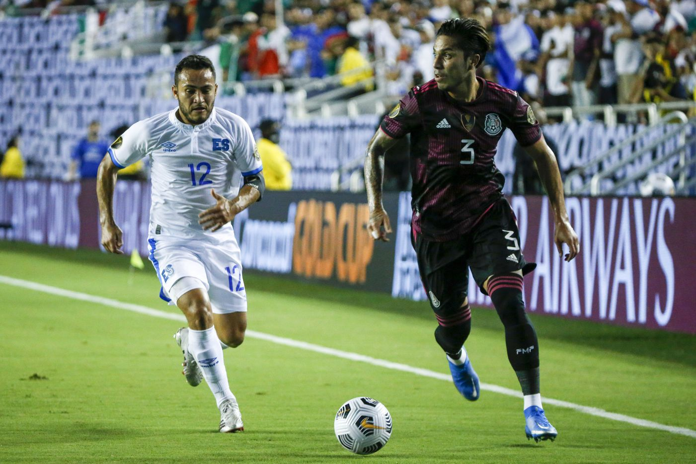 Mexico defender Carlos Salcedo (3) dribbles the ball ahead of El Salvador midfielder Marvin Monterroza (12) during the first half of a CONCACAF Gold Cup Group A soccer match at the Cotton Bowl on Sunday, July 18, 2021, in Dallas. (Elias Valverde II/The Dallas Morning News)