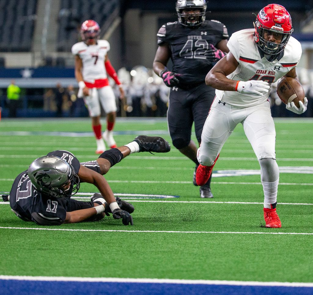 Cedar Hill wide receiver Brian Rainey (12) successfully pulls away from Denton Guyer defensive back Jaden Fugett (17) to score a touchdown right before halftime begins during the Class 6A Division II area-round high school football playoff game at the AT&T Stadium in Arlington, Texas, on Saturday, November 23, 2019. (Lynda M. Gonzalez/The Dallas Morning News)