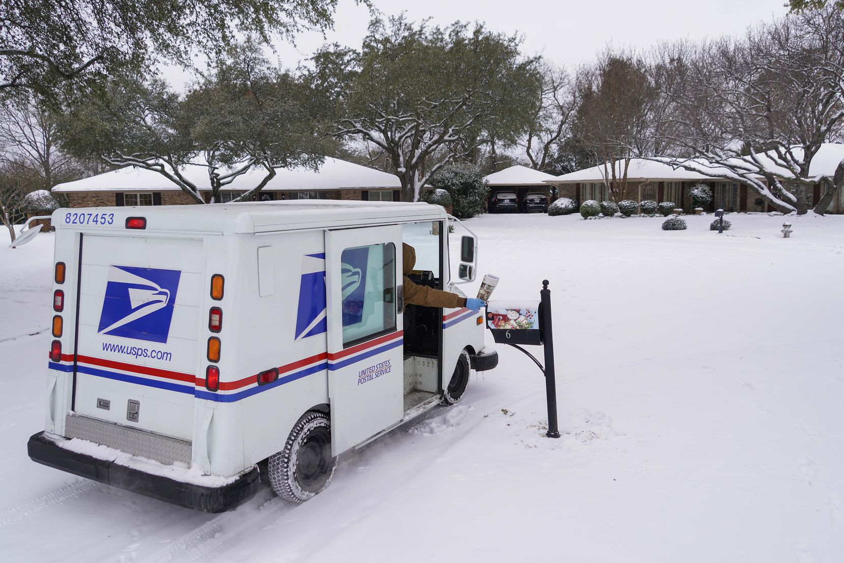 """Letter carrier Angel Garcia delivers mail to a snow covered neighborhood after a second winter storm brought more snow and continued freezing temperatures to North Texas on Wednesday, Feb. 17, 2021, in Richardson. """"We're going slow, but we are getting it delivered,"""" Garcia said of USPS mail deliveries."""