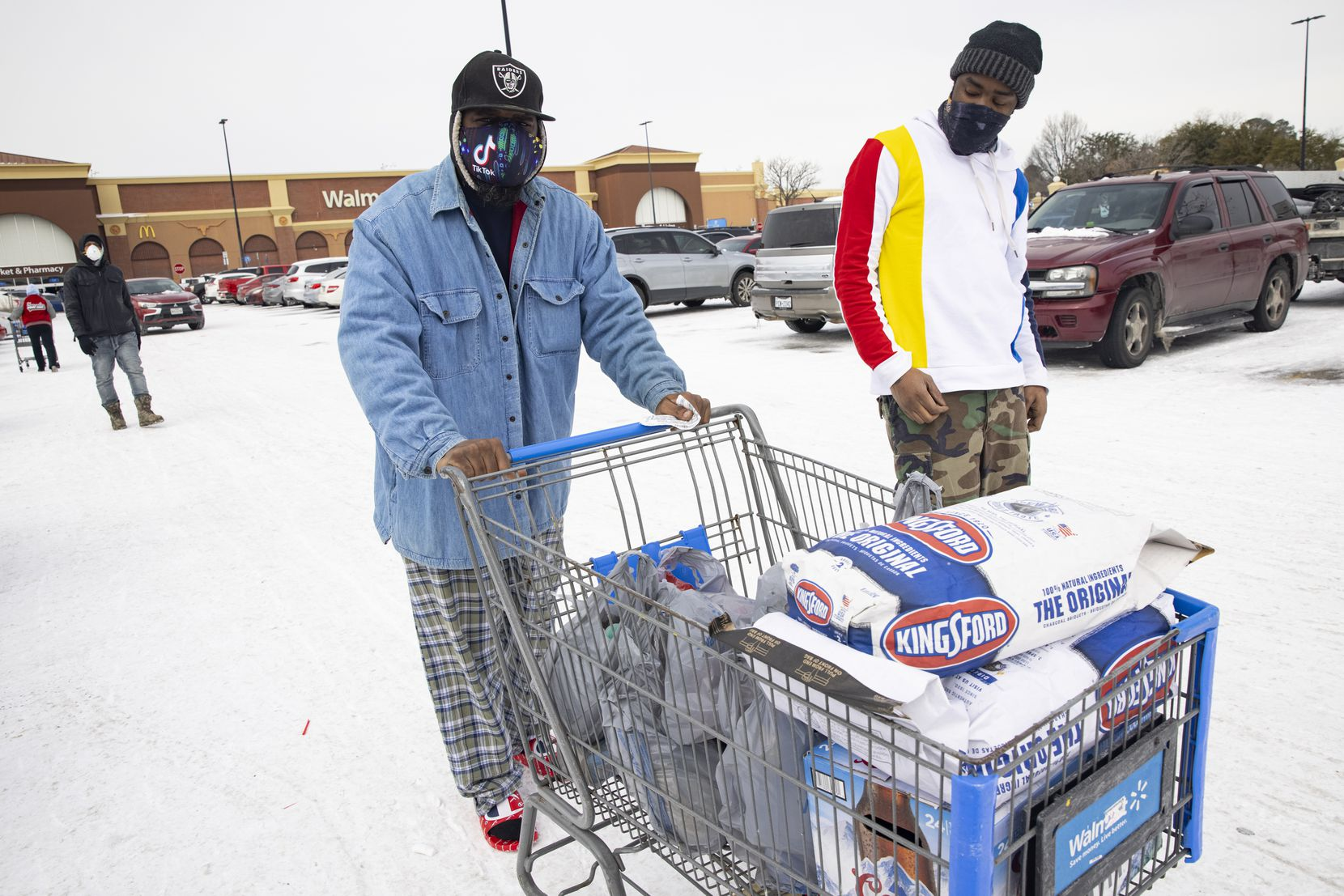 Reuben Brown (left) and Dekaetron McCalley wheel charcoal and a grill they bought at Walmart to their car at Walmart in Arlington. They lost power Monday and plan to use the charcoal and grill to cook food.