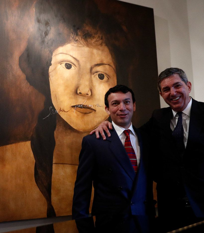 "European Union Ambassador to the U.S. Stavros Lambrinidis poses for a portrait with Artist René Alvarado, while standing in front of Alvarado's painting ""Linda Paloma."""