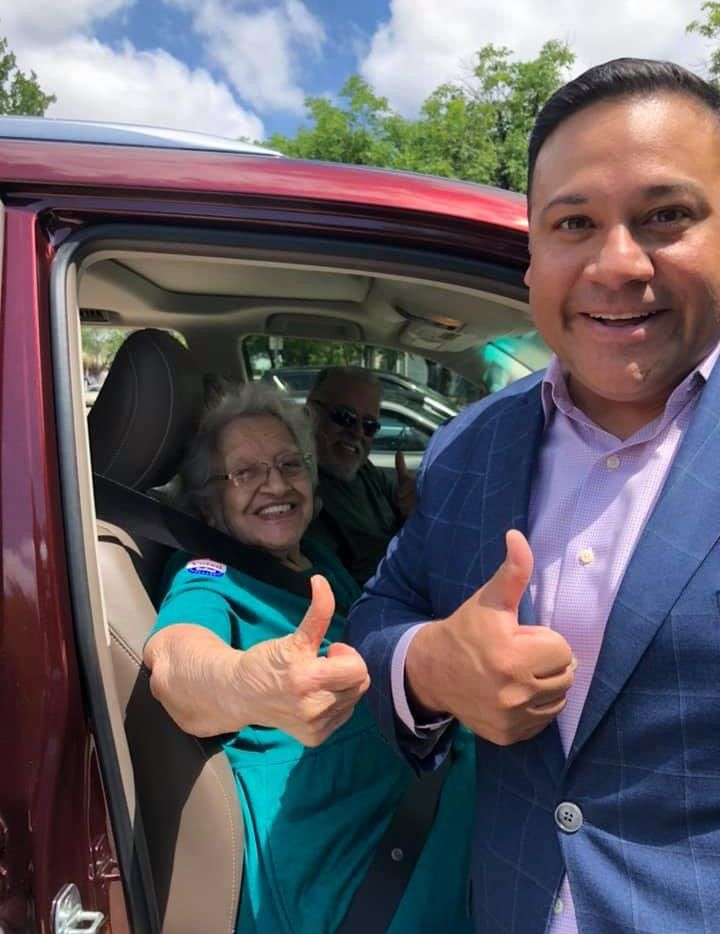 Jason Villalba helped his grandmother get to a drive-through voting station to vote.