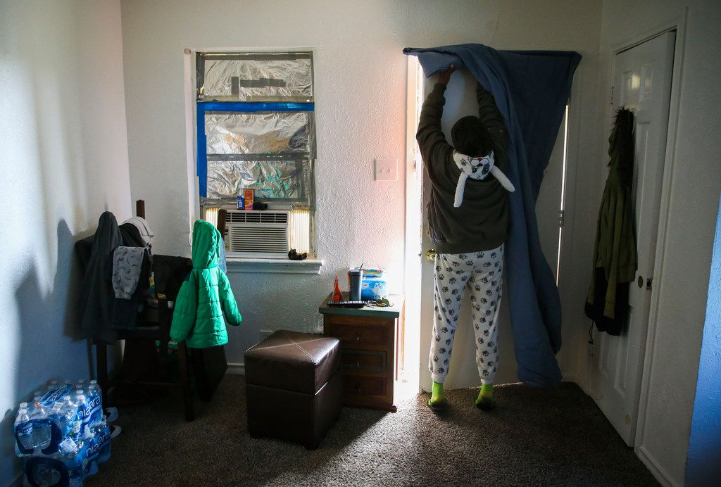 Dionne Lee, a Katrina evacuee who lives in this Bryan Song apartment with her two sons and 3-year-old grandson, hangs a blanket over the door to prevent drafts.