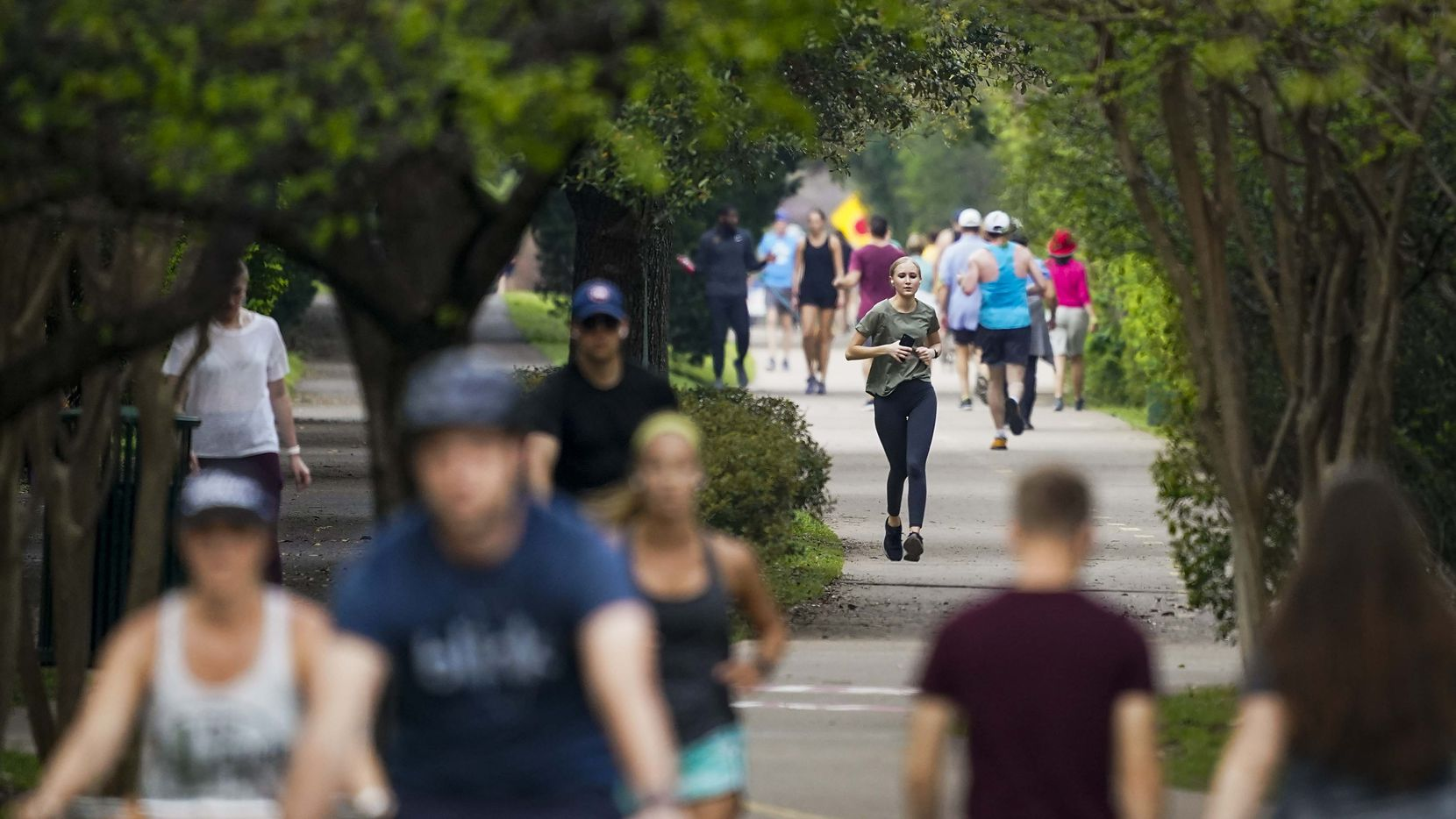 Runners, walkers and cyclists take to the Katy Trail near Knox Street on Thursday, March 19, 2020, in Dallas.  To encourage social distancing, the Katy Trail is urging people to consider alternative areas for walks and runs.