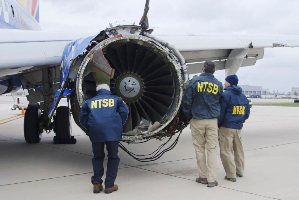 In this Tuesday, April 17, 2018 frame from video, a National Transportation Safety Board investigator examines damage to the engine of the Southwest Airlines plane that made an emergency landing at Philadelphia International Airport in Philadelphia.. (NTSB via AP)
