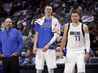 Dallas Mavericks center Kristaps Porzingis (center) reacts to a Mavs play against the Utah Jazz as head coach Jason Kidd and Luka Doncic (77) watch as well during a preseason game at the American Airlines Center in Dallas, Wednesday, October 6, 2021.