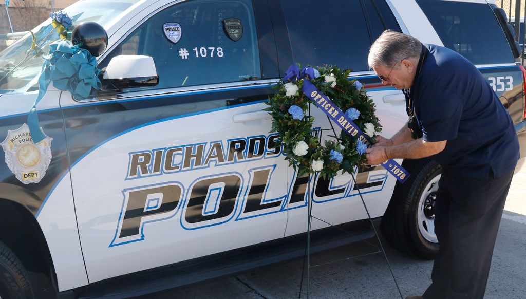 Retired California police officer Larry Powell delivers a wreath to the Richardson, Texas police headquarters on Thursday, Feb. 8, 2018. Larry works for Restland Funeral Home as a fleet manager and is a long time friend of the department. A Richardson police officer was fatally shot the night before at an apartment complex. A second person, 30-year-old Rene Gamez, who lived in the apartment complex, also died, police said. The suspect was identified Thursday as Brandon McCall. He is being held in the Collin County jail on a charge of capital murder of a police officer.