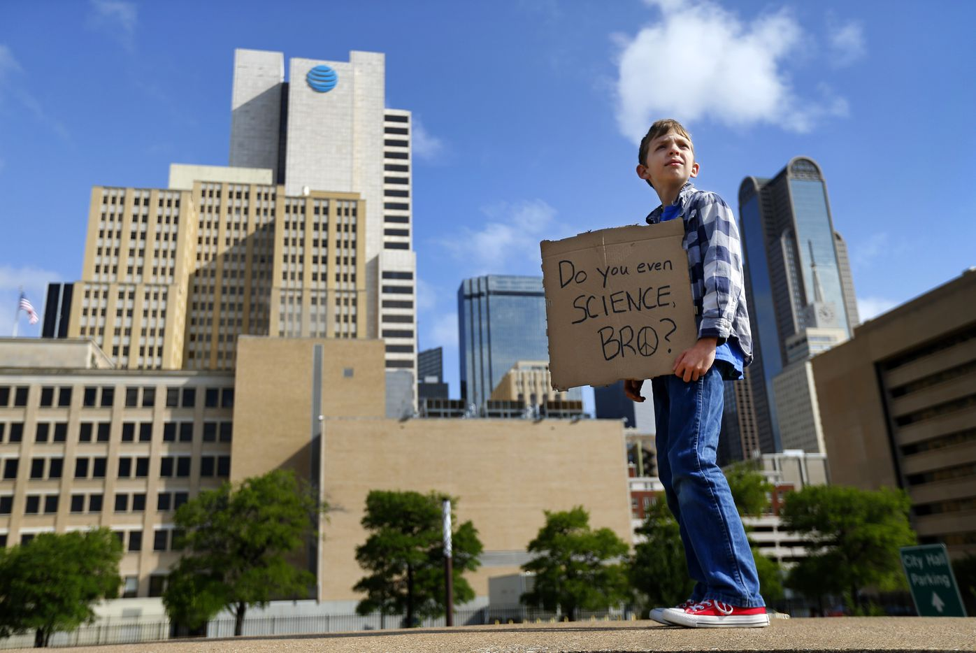 Martin Thomas, 10, of Dallas carries his homemade, pizza box sign as people gathered in downtown Dallas for the March For Science rally that kicked off at Dallas City Hall and ended at Fair Park's Earth Day celebration, Saturday, April 22, 2017. (Tom Fox/The Dallas Morning News)