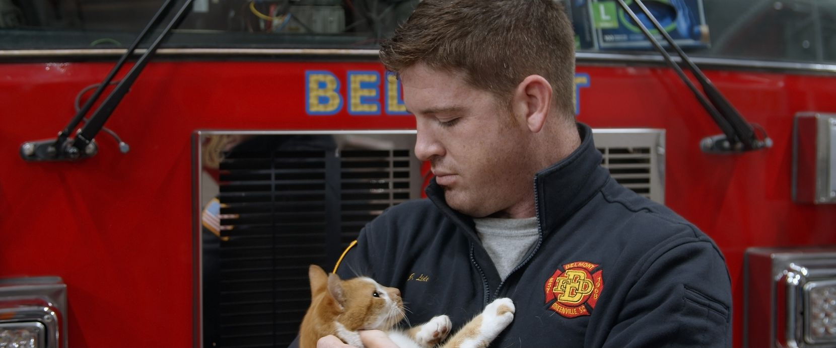 """A fire engineer holds Flame, who is taken care of by the Belmont Fire Department in Greenville, S.C., in """"Cat Daddies."""""""