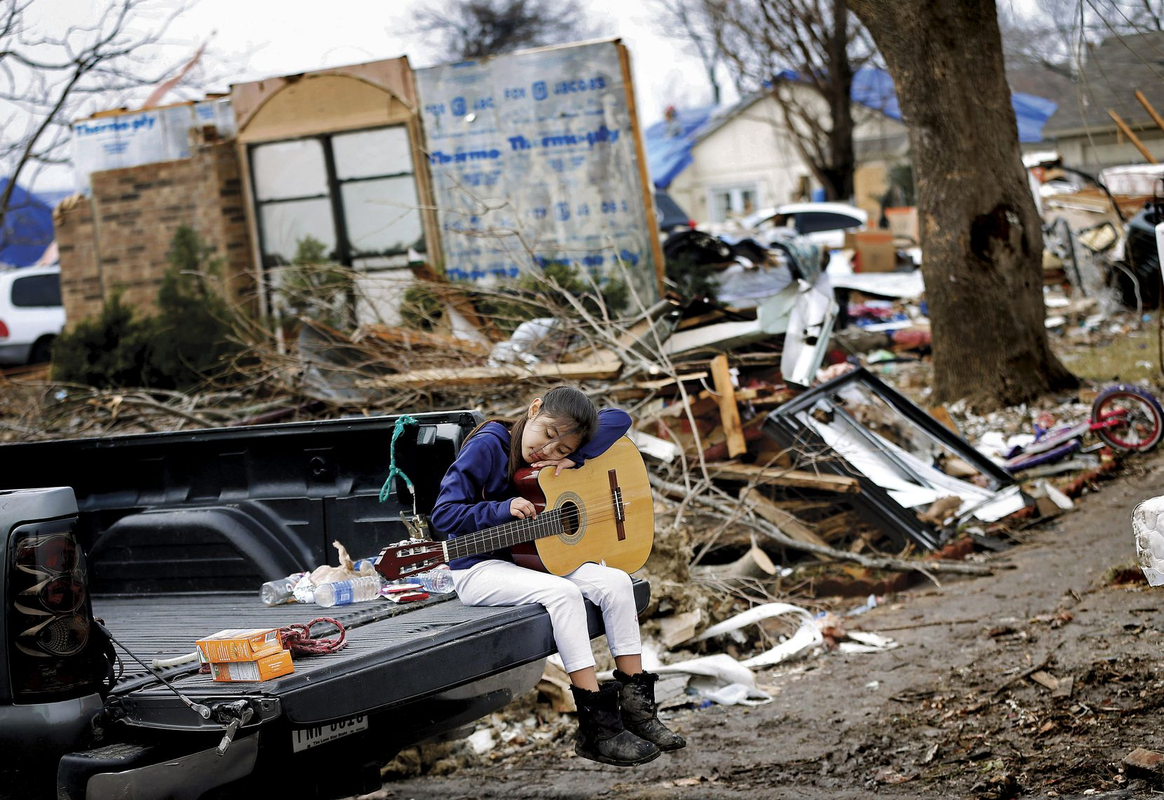 Natalie Rojas, 8, strummed a guitar found in the bedroom of her tornado-damaged home on Mariner Drive in Rowlett on Jan. 8. The guitar was a gift from her uncle.