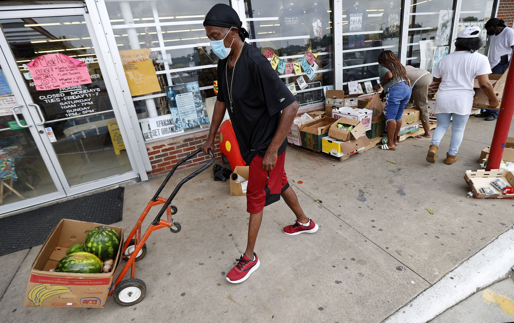 Van Hobbs found some watermelons and vegetables from a collection of donated food outside Pan-African Connection in Dallas, Thursday, July 2, 2020. (Tom Fox/The Dallas Morning News)