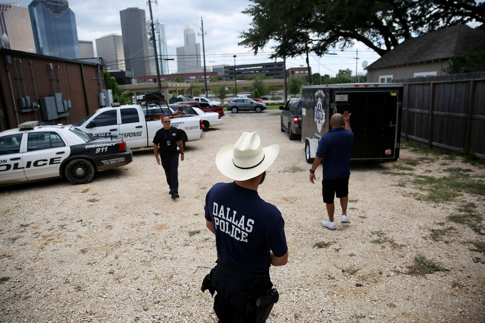 A Dallas police officer waits while a truck is backed in as members of the Dallas Police Association donate relief items collected for the Houston Police Department are dropped off at the Houston Police Officers' Union in Houston Wednesday August 30, 2017. The Dallas Police Association organized donations in assistance to police officers that are working following the devastation cause by Hurricane Harvey.