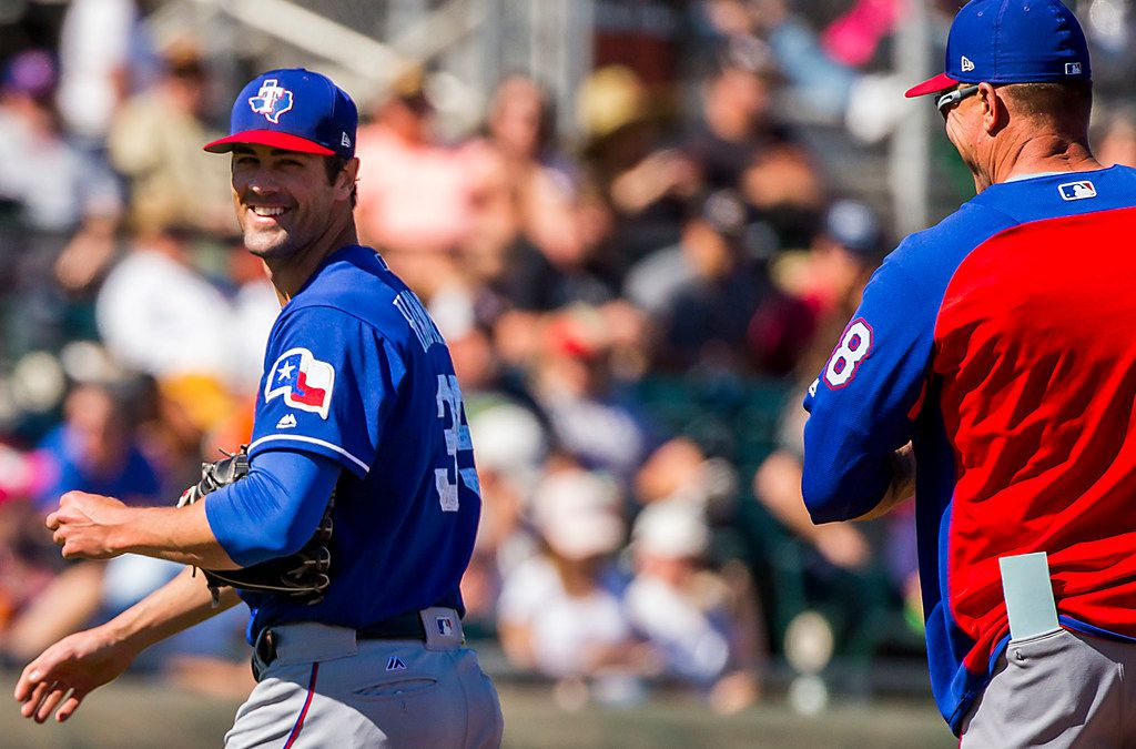Texas Rangers pitcher Cole Hamels laughs with manager Jeff Banister as he leaves the game during the third inning of a spring training baseball game against the San Francisco Giants on Saturday, March 3, 2018, in Scottsdale, Ariz. (Smiley N. Pool/The Dallas Morning News)