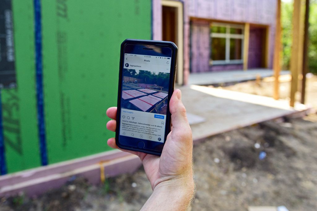 Connor Fagin displays a photograph of the foundation insulation before the eco-friendly passive design home took shape.