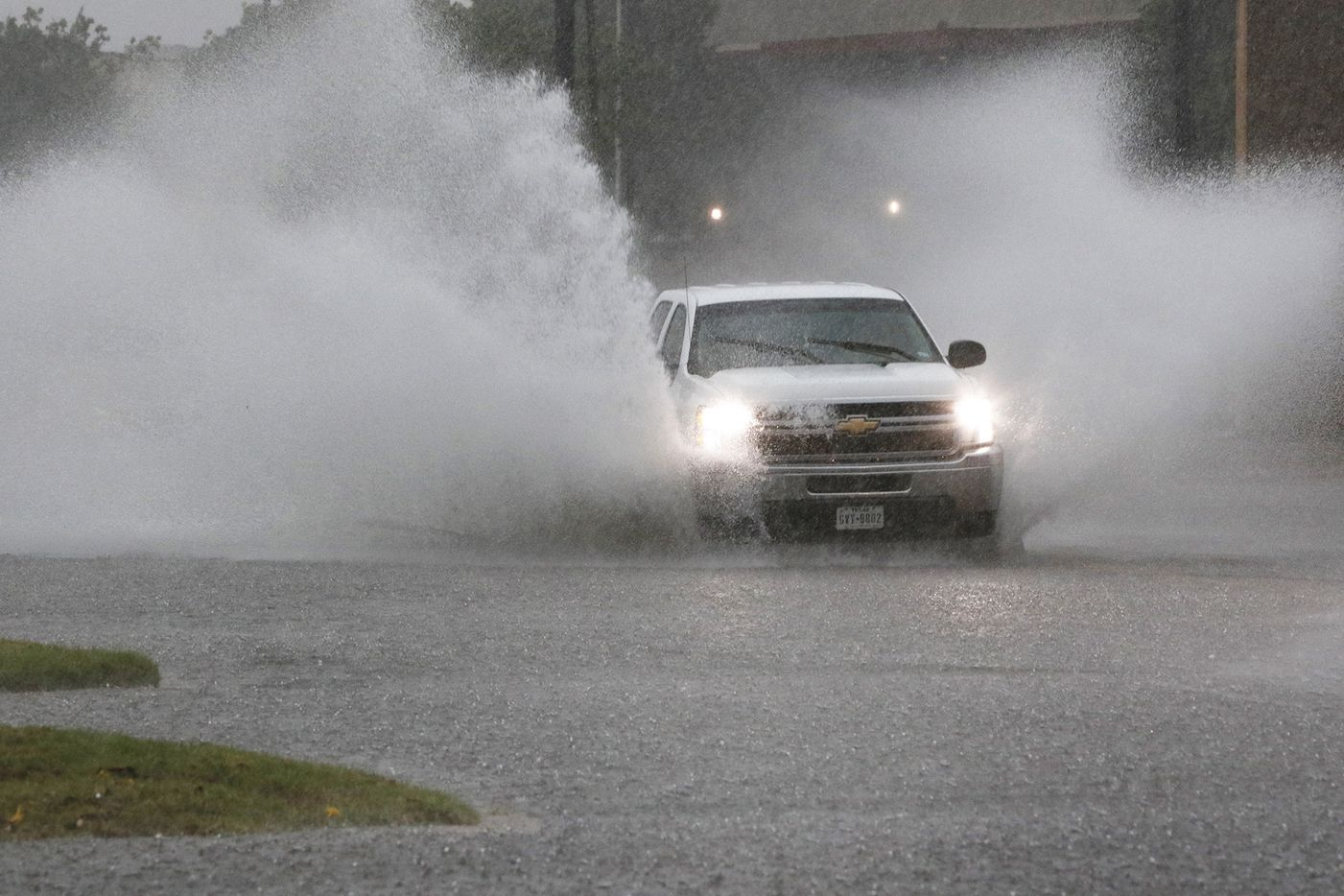 A truck drives through high water in Bedford during Friday afternoon's storms.