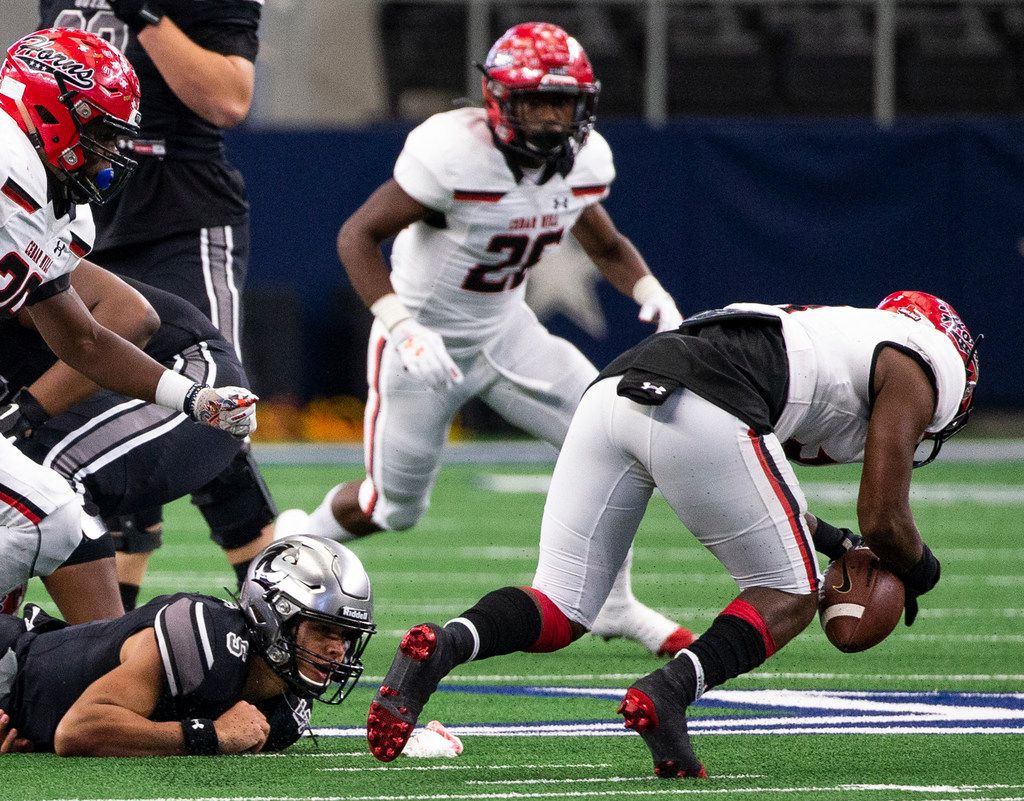 Denton Guyer quarterback Eli Stowers (5) watches as Cedar Hill free safety Dedryc Hutchings (right) recovers a fumbled ball during the Class 6A Division II area-round high school football playoff game at the AT&T Stadium in Arlington, Texas, on Saturday, November 23, 2019. (Lynda M. Gonzalez/The Dallas Morning News)
