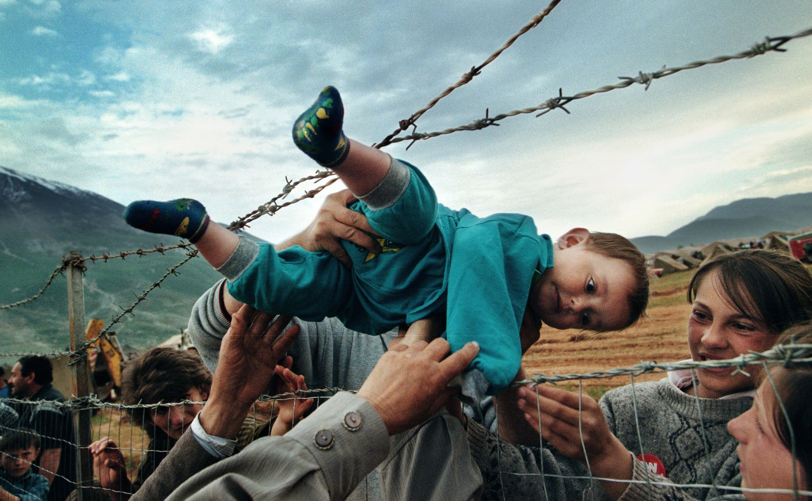 In this photo, part of Carol Guzy's Pulitzer Prize-winning portfolio, Kosovar refugee Agim Shala, 2 years old, is passed through the barbed wire fence into the hands of grandparents at the camp run by United Arab Emirates in Kukes, Albania. The members of the large Shala family were reunited here after fleeing Prizren in Kosovo during the conflict. . (The grandparents had just crossed the border at Morina). The relatives who just arrived had to stay outside the camp until shelter was available. The next day members of the family had tents inside. The fence was the scene of many reunions. When the peace agreement was signed, they returned to Prizren to find their homes only mildly damaged. There were tears of joy and sadness from the family as the children were passed through the fence, symbolic of the innocence and horror of the conflict.