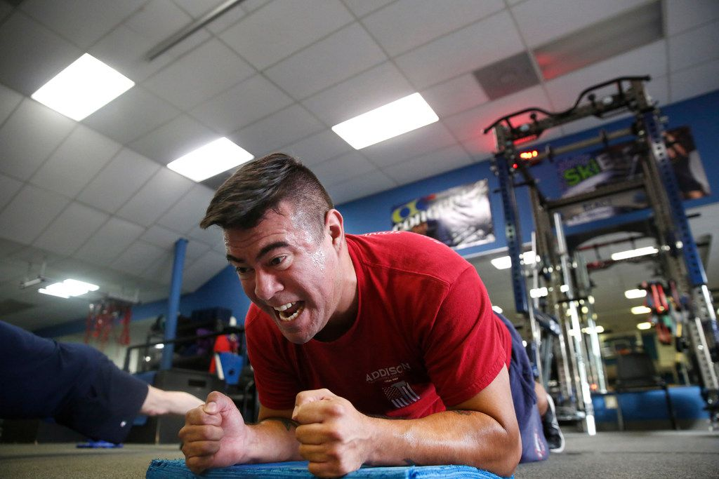 Addison firefighter/paramedic Steven Martinez holds a plank pose at REACT gym in Addison, Texas on Thursday, Jan. 24, 2019. The gym is now offering a free injury prevention training program to Addison first responders. (Rose Baca/Staff Photographer)