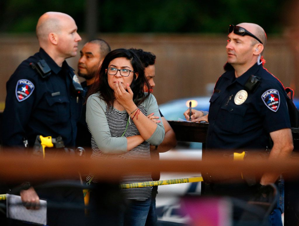 A woman who was gathered with employees visits with Arlington police who were investigating the shooting in which two people were killed at the Zona Caliente Sports Bar and Grill on S. Cooper St. in Arlington, Wednesday, May 3, 2017.