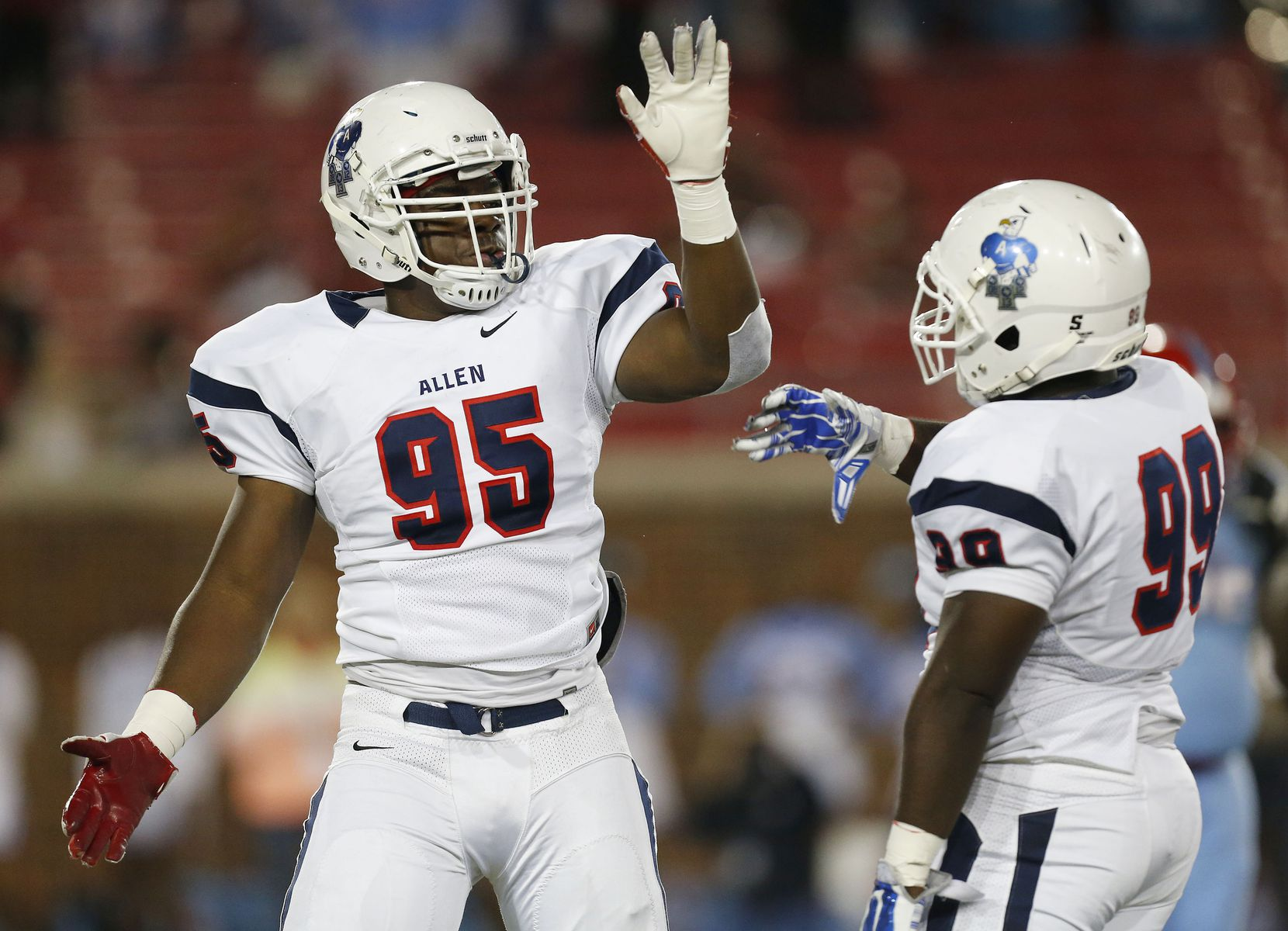 Allen defensive lineman Levi Onwuzurike (95) celebrates with defensive lineman Ryan Hinmon (99) after making a tackle in the first quarter during the UIL class 6A division I state semifinal high school football game between Allen and Skyline at Gerald J. Ford Stadium in Dallas Saturday December 13, 2014. (Andy Jacobsohn/The Dallas Morning News)