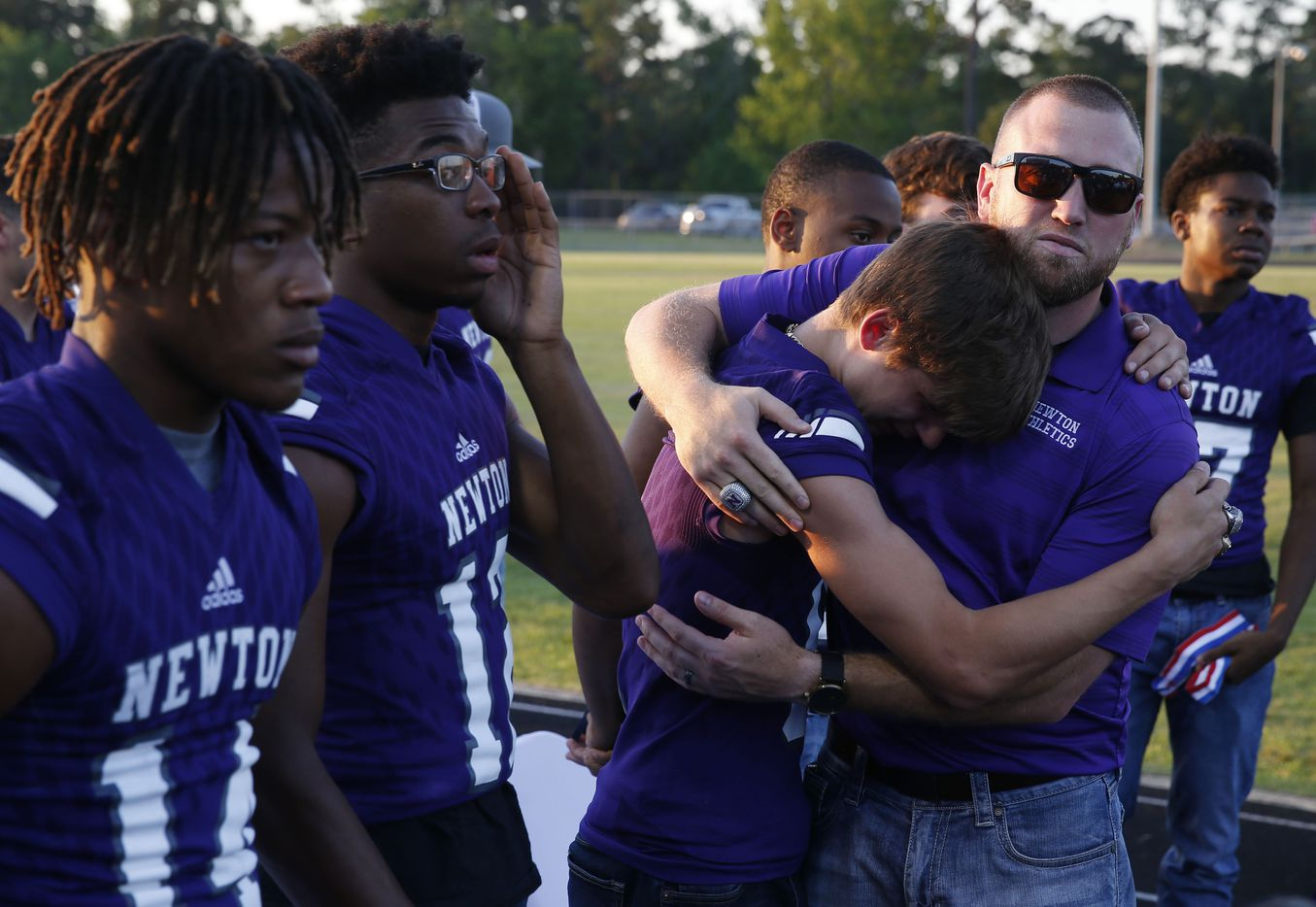 """Current head football coach and son Drew Johnston hugs Newton's Nate Williams (6) during the memorial service for Newton High School head football coach William Theodore """"W.T."""" Johnston at Curtis Barbay Field at Newton High School in Newton, Texas on Wednesday, May 15, 2019. (Vernon Bryant/The Dallas Morning News)"""