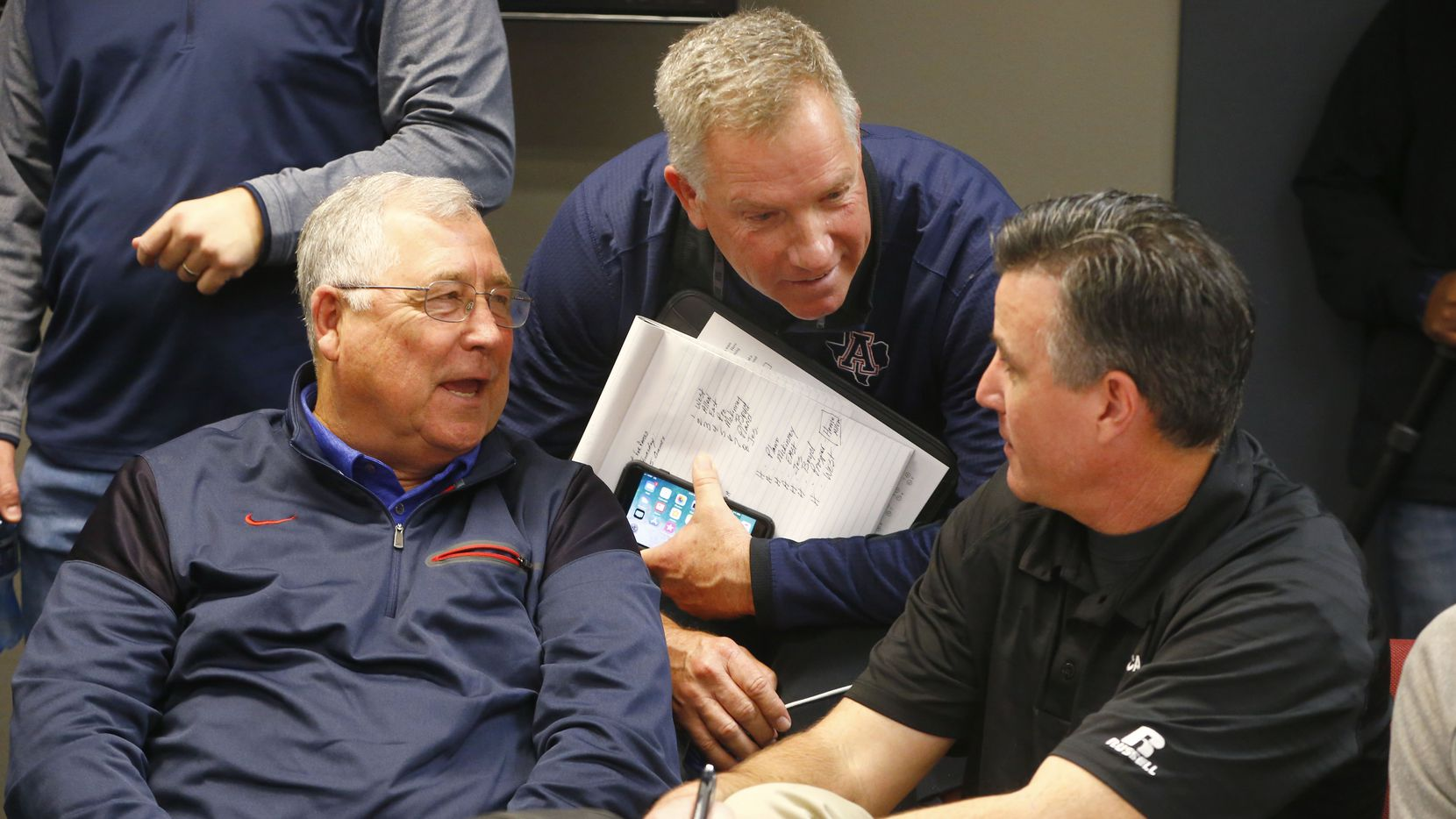 Allen's Steve Williams (from left) talks with head football coach Terry Gambill with Plano's assistant athletic director Ralph Hinds during the UIL alignment announcement at Birdville Fine Arts/Athletics Complex in North Richland Hills, Texas on Feb. 1, 2018.