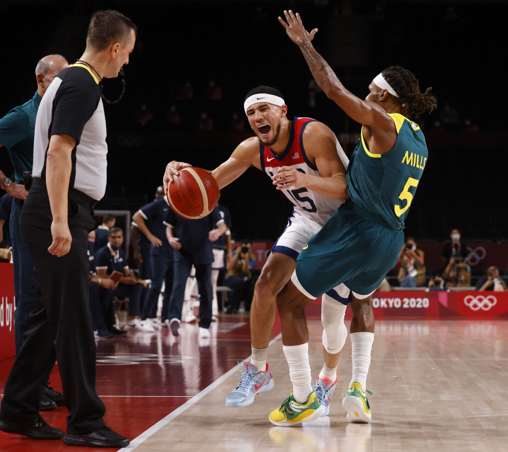 USA's Devin Booker is fouled by Australia's Patty Mills (5) during the second half of a men's basketball semifinal at the postponed 2020 Tokyo Olympics at Saitama Super Arena, on Thursday, August 5, 2021, in Saitama, Japan. USA defeated Australia 97-78 to advance to the gold medal game. (Vernon Bryant/The Dallas Morning News)