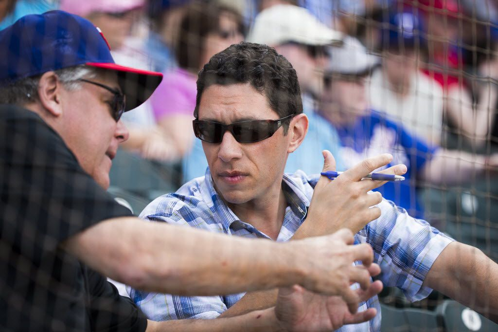 Texas Rangers General Manager Jon Daniels  (facing) talks with Neil Leibman, Rangers  ownership committee chairman during a spring training game against the Kansas City Royals at Surprise Stadium on Thursday, March 3, 2016, in Surprise, Ariz. (Smiley N. Pool/The Dallas Morning News)