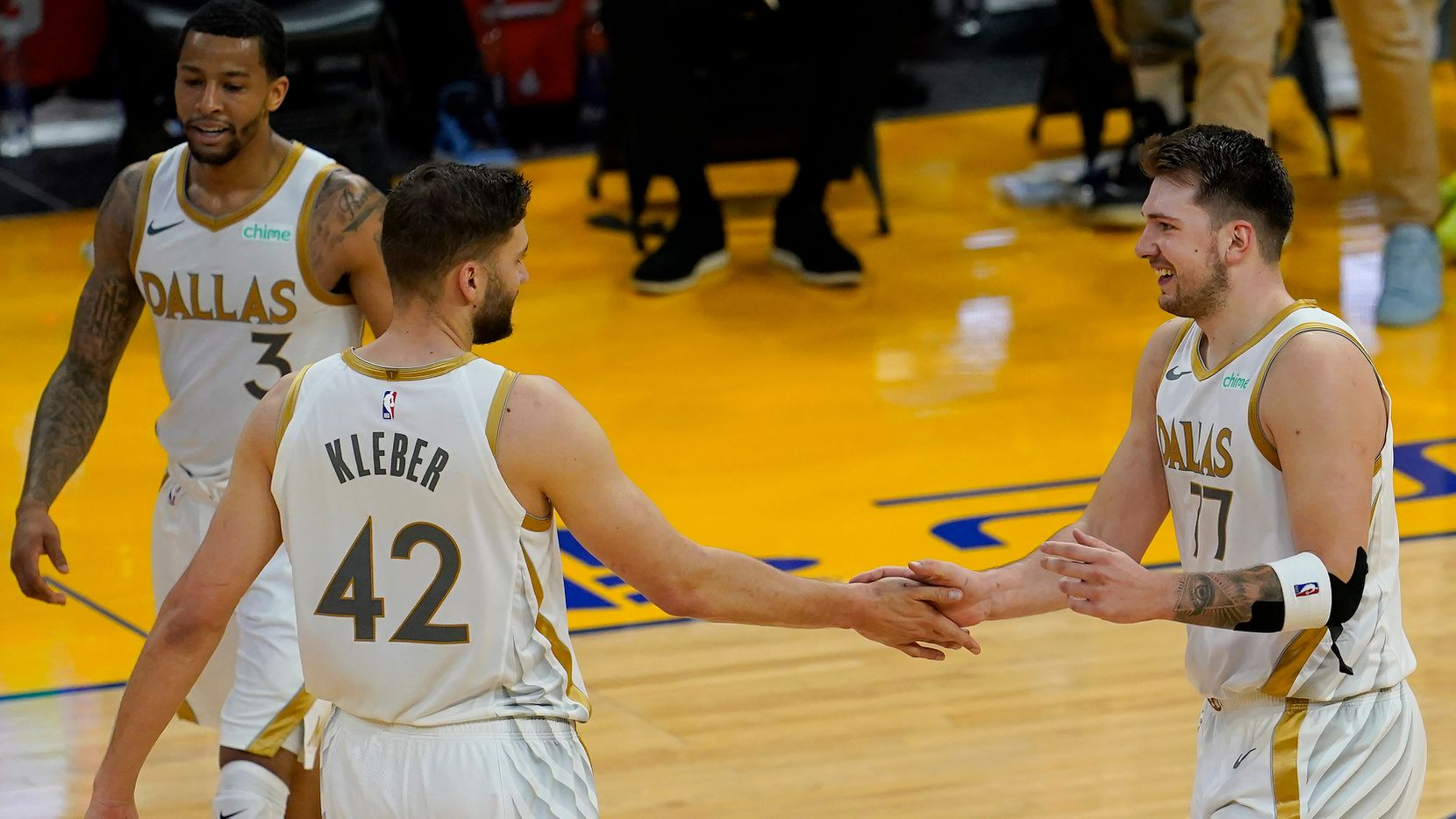 Dallas Mavericks guard Luka Doncic, right, celebrates with Maxi Kleber (42) and Trey Burke (3) during the first half of an NBA basketball game against the Golden State Warriors in San Francisco, Tuesday, April 27, 2021.