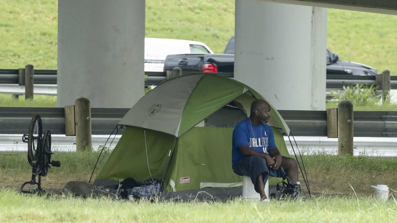 A man sits outside his tent underneath I-35 near downtown on Wednesday, Aug. 18, 2021, in Dallas. (Elias Valverde II/The Dallas Morning News)