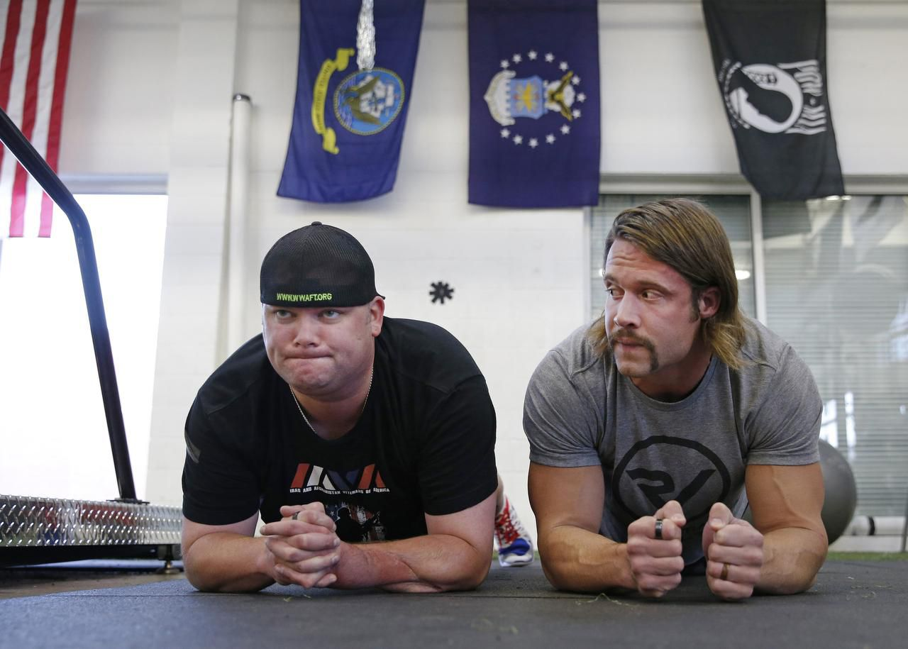 Jacob Schick (left), an injured military veteran, works on physical training with David Vobora, a former NFL linebacker who trains both injured veterans and disabled athletes at his Performance Vault gym in Dallas.
