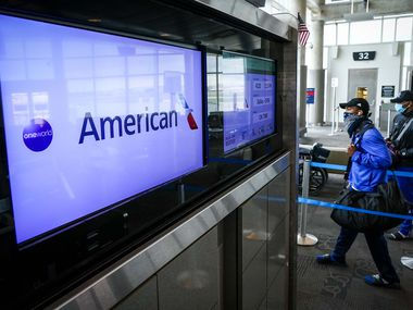Passengers wearing face masks due to the new coronavirus board an American Airlines flight to DFW Airports at Hobby Airport in Houston on Friday, March 20, 2020.