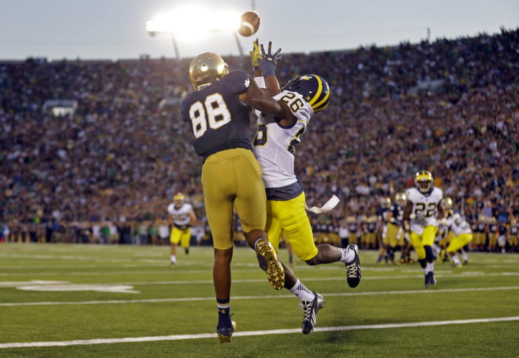 FILE - In this Sept. 6, 2014, file photo, Michigan defensive back Jourdan Lewis, right, interferes with Notre Dame wide receiver Corey Robinson as he attempts to make a catch in the end zone during the first half of an NCAA college football game in South Bend, Ind. (AP Photo/Michael Conroy)